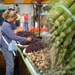 Persona comprando en un mercado de frutas a vendedores minoristas.