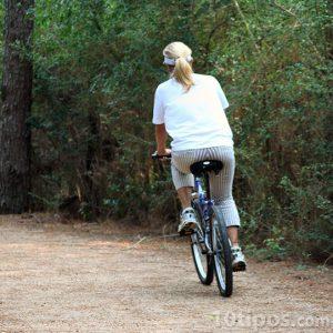 Mujer en bicicleta paseando por el bosque