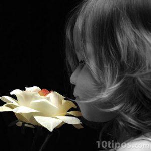 Niña oliendo una flor de color blanca