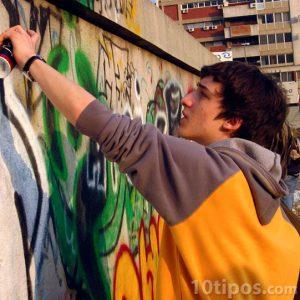 Adolescente haciendo graffiti en las calles
