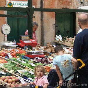 Personas comprando verduras en la calle