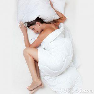 Mujer dormida con colchas blancas