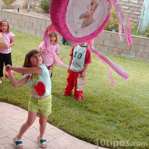 Niña golpeando la piñata en cumpleaños