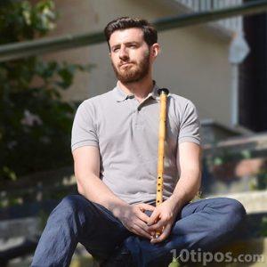 Hombre posando con su flauta hecha de bambú