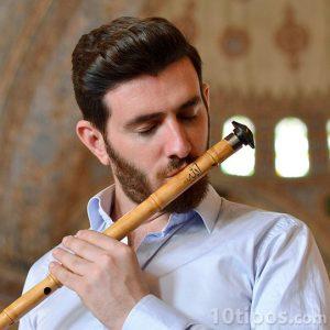 Hombre tocando flauta hecha de bambú