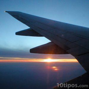 Avión en pleno vuelo donde se ve el sol en el horizonte