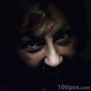 Mirada de mujer furiosa saliendo de la obscuridad