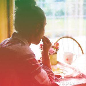Mujer desayunando y comiendo con la mano