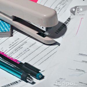 Engrapadora, pluma y papeles