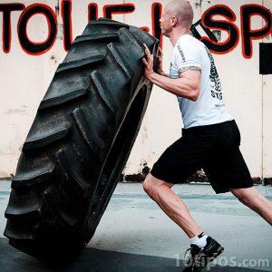 Atleta levantando neumático como ejercicio