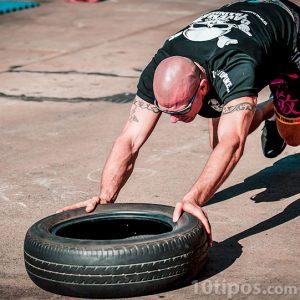 Hombre haciendo ejercicio con un neumático