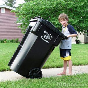 Niño empujando el bote de basura