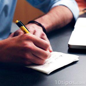 persona escribiendo en un pedazo de papel