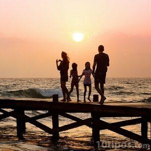 Familia en un muelle al atardecer