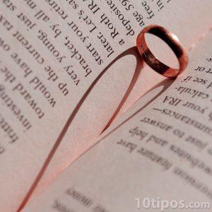 Anillo haciendo un corazón con su sombra dentro de un libro