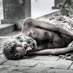 Persona en situación de calle acostada en el piso