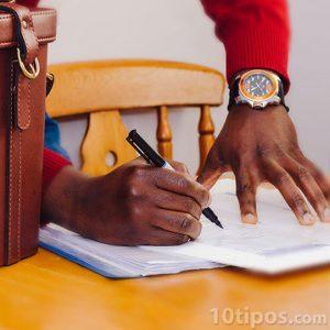 Persona firmando documento con pluma fuente