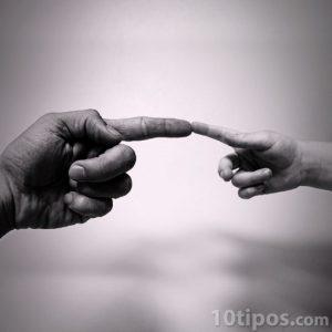Mano de un adulto señalando otra mano de un menor