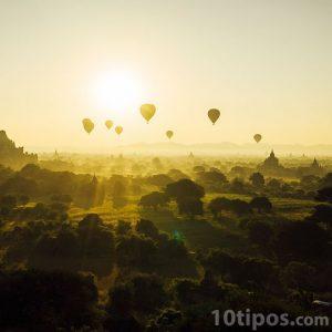 Paisaje al amanecer con globos en el cielo