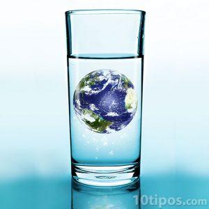 Vaso de agua con pequeño planeta tierra dentro