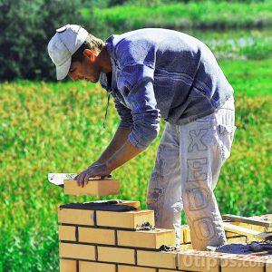 Albañil haciendo una pared de ladrillos