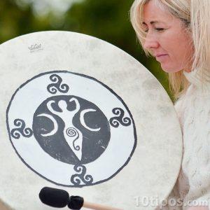 Mujer tocando tambor de piel animal