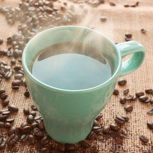 Taza de café recién hecho sobre mesa con granos de café molido