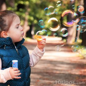 Niña soplando burbujas de jabón