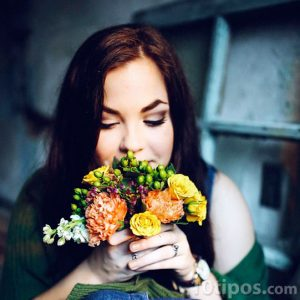 Mujer oliendo flores
