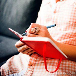 Persona escribiendo en una libreta roja