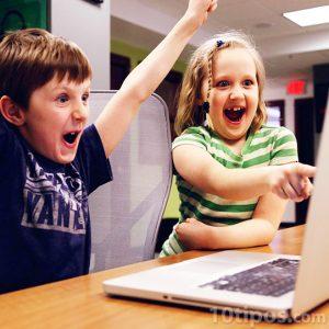 Infantes divertidos frente a la computadora