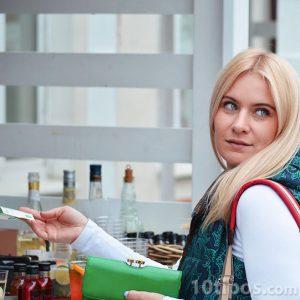 Mujer pagando un café con efectivo
