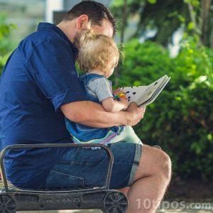 Papa leyendo a su hijo sentado en sus piernas