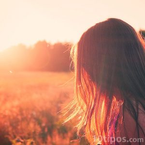 Mujer de cabello largo viendo el atardecer